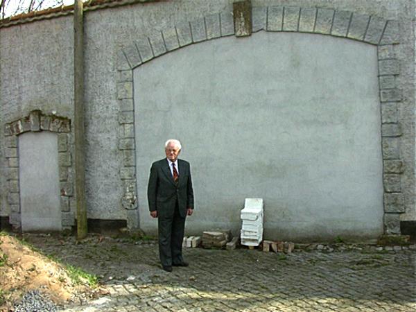 Friedrich Klingenberg vor den von ihm als Häftling des Männerlagers gemauerten Bögen in der Ravensbrücker Lagermauer (Dreharbeiten 1995)