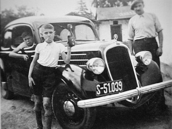 Walter Morgenbesser mit Zigarette vor einem Auto der Firma Pollak. (Quelle: Privat W. Morgenbesser)
